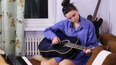Young beautiful girl learning to play the guitar at home Stock Footage