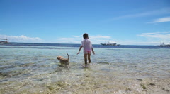 Girl playing with a dog on the beach Stock Footage
