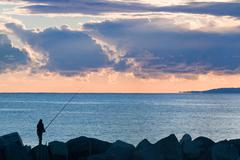 man fishing  with calm sea and stormy clouds at dusk - stock photo