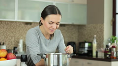 Young woman adding pepper to her soup at the stove in kitchen HD Stock Footage