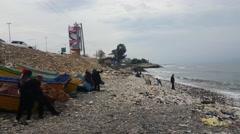 Side view of Iranian men women wearing Islamic hijab looking at the Caspian sea. - stock footage