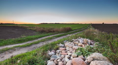 4k timelapse of sunset over fields and rural road - stock footage