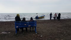 Rear view of Iranian men women wearing Islamic hijab looking at the Caspian sea. Stock Footage