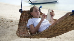 Girl in the hammock with the tablet on the beach Arkistovideo