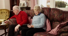 Senior couple browsing the internet on their tablet tablet. Shot on RED Epic. - stock footage