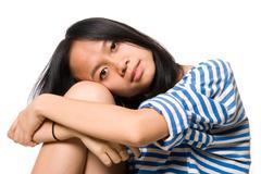 Portrait of girl put head on knees - stock photo