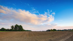 4k timelapse of beautiful sunset sky with clouds over plowed field. - stock footage