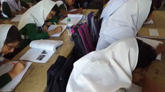 Muslim students with hijab in school studying writing in handbooks listening - stock footage