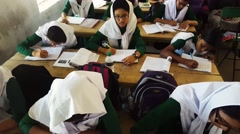 Muslim students with hijab in school studying writing in handbooks listening Stock Footage