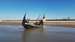 Fishermen in a traditional Bangladeshi fishing boat on the shore Stock Footage