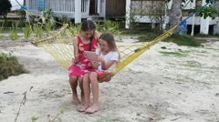 Girls in the hammock with the tablet on the beach Stock Footage