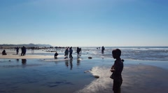Crowd of silhouette people walking in a beach in a sunny day - stock footage