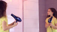 Beautiful little girl dries hair a hairdryer before mirror Stock Footage