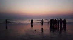 Crowd of silhouette people walking taking picture with mobile in a beach, sunset - stock footage