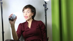 Stock Video Footage of Beautiful emotional model posing at camera with light equipment