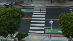 Woman with a yoga mat crossing the zebra walk - stock footage