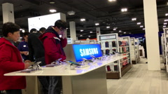 People trying new cellphone inside Best buy store - stock footage