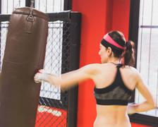Beautiful girl boxing against punching bag (intentionally blurred) - stock photo