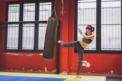 Beautiful girl boxing against punching bag Stock Photos