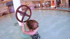 Toddler girl swimming in indoor pool of The Trails Recreational Center. Stock Footage