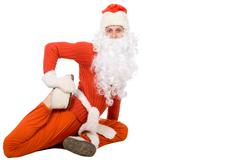 Santa Claus sit on half twine and stretching - stock photo