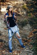 Full length portrait of fashionable young woman wearing torn jeans in forest Stock Photos