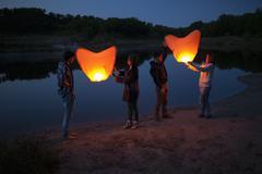 Full length of hikers releasing paper lanterns at lakeshore - stock photo