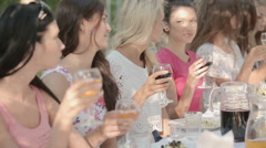 Company of young women drinking wine outdoors Stock Footage