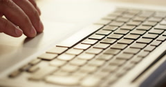Closeup detail view of male hands typing furiously on a laptop. - stock footage