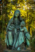 Mother Mary Christianity Religion in Nature in Cemetery Graveyard - stock photo