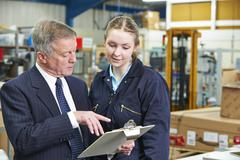 Factory Manager And Apprentice Engineer Looking At Clipboard - stock photo