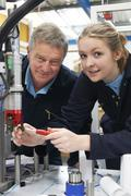 Engineer And Female Apprentice Working On Machine In Factory - stock photo