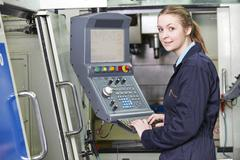 Female Apprentice Engineer Operating Computerized Cutting Machine - stock photo