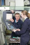 Apprentice And Engineer Using Computer Controlled Cutting Machine - stock photo