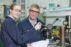 Engineer Showing Female Apprentice How To Use Drill Stock Photos