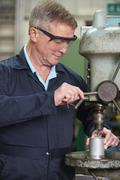Engineer Using Drill In Factory - stock photo