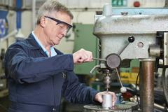 Skilled Engineer Using Drill In Factory - stock photo