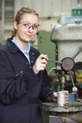 Female Apprentice Using Drill In Factory Stock Photos