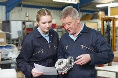 Engineer With Apprentice Looking At Component In Factory - stock photo