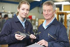 Apprentice Engineer Measuring Component With Micrometer - stock photo