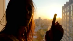 Girl touching the sunlight by hand in her room at home. Happy woman looking at Stock Footage