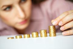 Woman stacking gold coins into increasing columns - stock photo