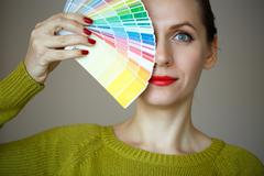 Stock Photo of Woman with a red lips looking to a color  palette