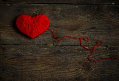 Stock Photo of Red heart shape made from wool on old shabby wooden background
