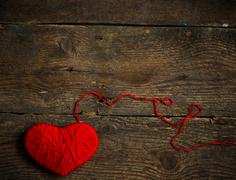 Red heart shape made from wool on old shabby wooden background - stock photo