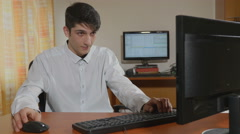 Handsome young programmer bored playing at work Stock Footage