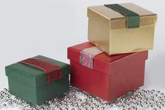 Three presents with ribbons, gold, green and red, isolated - stock photo