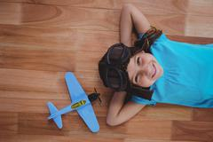 Smiling girl laying on the floor wearing aviator glasses and hat Stock Photos