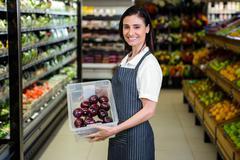Pretty brunette holding box of vegetable Stock Photos