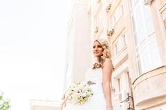Beautiful bride in magnificent dress stands alone on stairs - stock photo